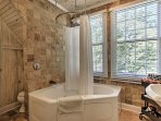 This en-suite master bathroom offers stone tiling, a jetted tub and a rain shower head.