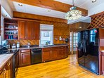 The fully equipped kitchen offers cherry cabinets and modern appliances.