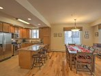 The kitchen island offers seating for 3, while the dining table provides seating for 8-10 guests.