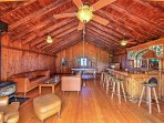 A restored barn has been converted into an entertainment room with a pool table, bar, wood-burning stove, piano, and a...