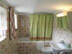 Bad im Keller mit Badewanne, Bidet, Waschbecken und Nachtspeicherofen.