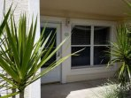 Condo entrance, surrounded by tropical foliage, with covered guest parking conveniently located infront of unit.