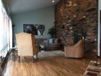 Living room with brick-adorned wall. Makes great for entertaining!