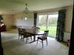 Dining room which adjoins living room. French windows to lawned area at side of bungalow.