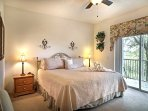 The master bedroom boasts a king-sized bed and doors to access the patio.