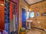 The cabin includes a vibrant second bathroom downstairs with a walk-in shower and single vanity.