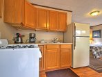 The kitchen boasts plenty of counter space and wooden cabinets.