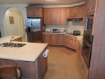 Kitchen has stainless steel appliances and  cooking utensils