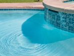 Heated pool with integrated waterfall spa
