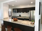 Fully-equipped kitchen with granite counter tops and island with additional seating.