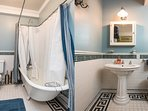 Victorian bathroom with claw foot tub, pedestal sink, hair dryer,  and decorative tile borders