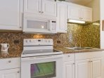The kitchen has beautiful granite counter tops and backs plash.