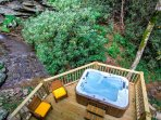 A relaxing hot-tub and deck over a running stream at the Waterfall Cabin