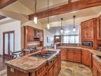 The kitchen features ample lighting, beautiful countertops, and a center island.