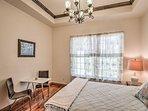 This bedroom offers a queen bed beneath an elegant chandelier.