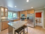 Join the cook in the fully equipped kitchen featuring stainless steel appliances and granite countertops.