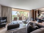 The living room, opening on the balcony, overlooks the pools.
