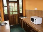 Fully equipped pantry with microwave, refrigerator, cooker, kettle, toaster, cutlery, crockery.