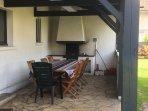 La terrasse couverte avec cheminée extérieure et grande table