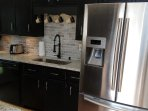 Modern full kitchen with Keurig,electric range and oven,toaster,micfrowave,pots,pans,silverware