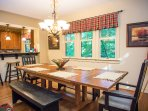 Open concept dining area with breakfast bar seating at the kitchen and access to the back porch