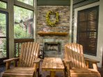 Relax around the fireplace on the screened in back porch