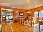 Follow the hall to the spacious dining room/kitchen area, featuring an elegant wood table and a rustic deer-antler...