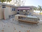 Outdoor deck with retractable shade awning, bbq, picnic table and outdoor shower.