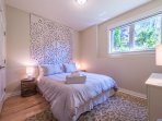 Lower Level Bedroom with Luxurious Touches, top level bedding and bed. Garden view with peonies.
