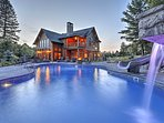 This Lake Placid home's state of the art pool features  waterfalls, a slide, and views of the Adirondack mountain range!
