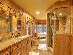 This luxurious bathroom features a boutique claw footed tub surrounded by large windows with views of the serene...