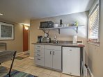This kitchenette comes complete with a mini fridge, microwave, coffeemaker and electric cooktop.