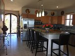 Kitchen  equipped with stainless steel appliances, microwave, oven, refrigerator, dishwasher, and 5 burner cook top