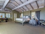 High ceilings and exposed beams give the master suite an open feel.  There's a tv in the master suite as well.
