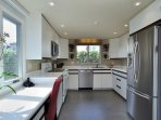 The sleek, modern kitchen has a Samsung stainless steel refrigerator, Miele dishwasher, microwave, built-in desk, and ...