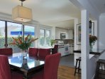 The red dining chairs really pop in this open living space. There's seating for 6 at the table and room for 2 more at ...