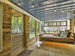 Relax in the screened porch - enhanced in charm with string lights - to admire the home's wilderness surroundings.