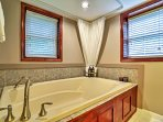 This full-sized romantic garden tub offers a retractable handheld shower for guests to enjoy!