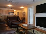 #209 Living room with fireplace, TV, looking thru to kitchen.