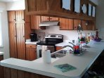 Kitchen is clean and stocked with necessary cooking items and dishes