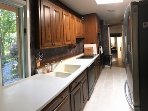 A full equipped kitchen with garden view and new porcelain tile at Rochester Vacation House
