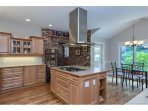 Kitchen with stainless steel appliances, eat-in and door to BBQ/patio.