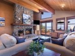 Living room with stone fireplace and lake views