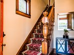 Entry foyer with original staircase, leaded beveled glass window and architectural trim details.