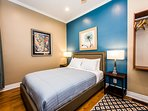 Bedroom suite 2 with private ensuite bathroom, comfortable furnishings, TV and original artworks.
