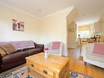 A comfortable sitting room with sofa & tub chairs and open plan to the dining area & kitchen.