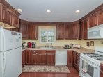 Large kitchen with cherry wood cabinets and gas cooking range.