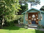 ...and pretty summerhouse with comfy sofa and chairs