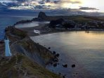 Castlepoint lighthouse, with Castle Rock at the rear. Great walking track for average fitness folk.