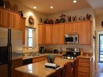 Upscale stainless and granite kitchen shows view to front entry
